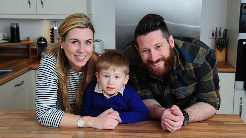 Vikki and Edward with their son in their new home