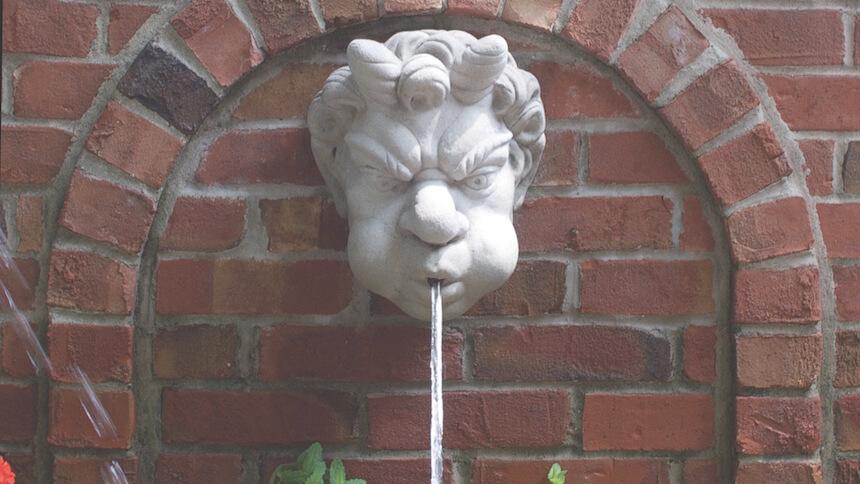 Grotesque wall fountain