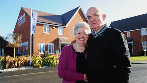 The Adams' outside their new home